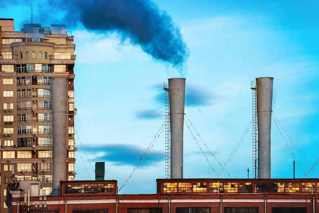Przemysłowy czarny toksyczny dym z elektrowni węglowej na błękitnym niebie