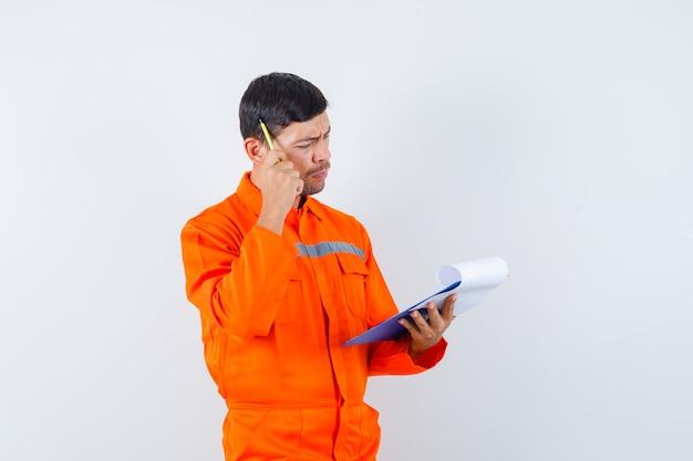 Przemysłowy człowiek przeglądający notatki w schowku w mundurze i zamyślony. przedni widok.
