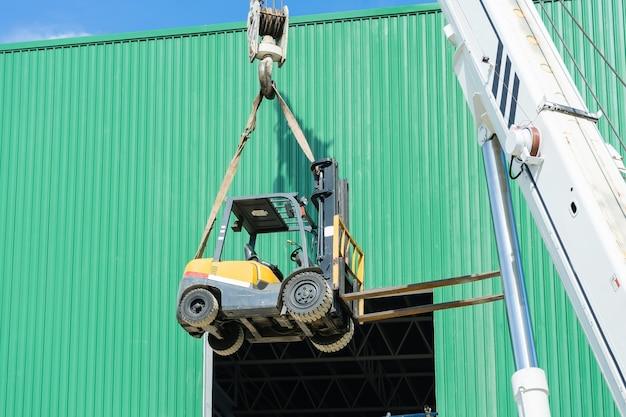 Przemysłowy dźwigowy działający i podnosi forklift w świetle słonecznym i niebieskim niebie