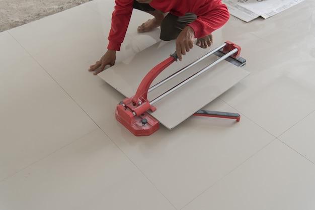 Przemysłowy kaflarz budowniczego pracownik pracuje z podłoga