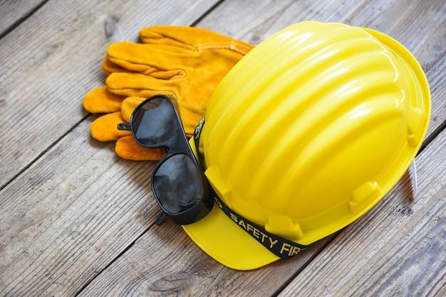 Przemysłowy kask ochronny, rękawiczki i okulary w żółtym kapeluszu