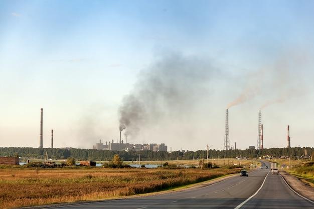 Przemysłowy krajobraz miasta z wieloma fabrykami, autostradami i wieżowcami. zanieczyszczenie środowiska