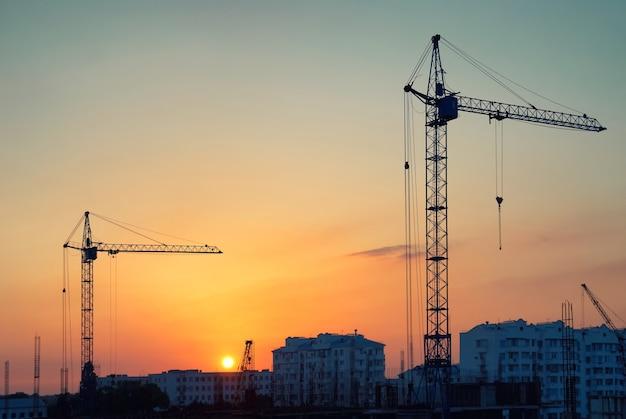 Przemysłowy krajobraz z sylwetkami dźwigów na tle zachodu słońca
