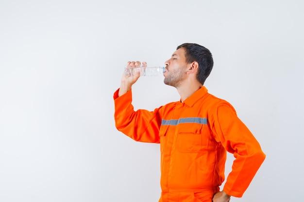 Przemysłowy mężczyzna pije wodę w mundurze i wygląda na spragnionego. .