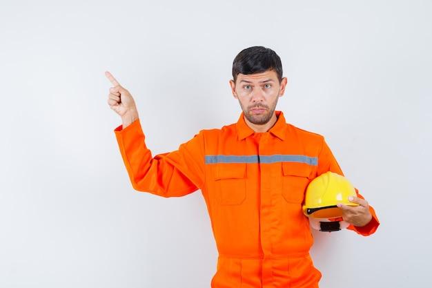 Przemysłowy mężczyzna trzyma hełm, wskazując na lewy górny róg w jednolitym widoku z przodu.