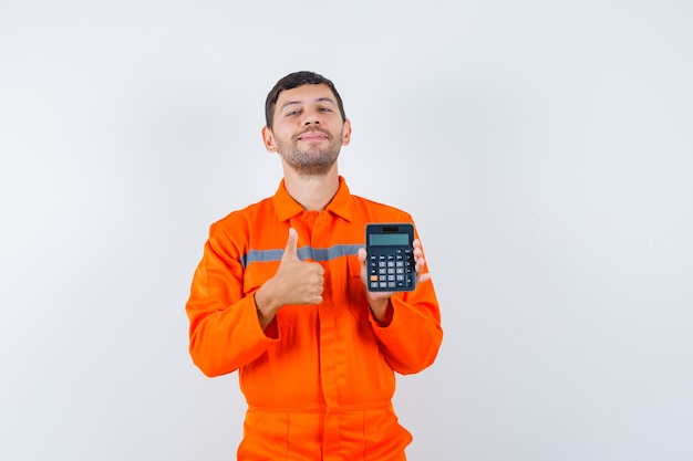 Przemysłowy mężczyzna trzyma kalkulator, pokazuje kciuk w mundurze i wygląda wesoło. przedni widok.