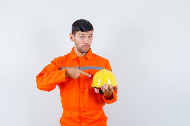 Przemysłowy mężczyzna, wskazując na hełm w mundurze, widok z przodu.