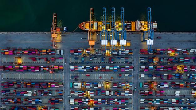 Przemysłowy port morski pracujący w nocy z kontenerowcem pracującym w nocy, widok z lotu ptaka kontenerowiec załadunku i rozładunku w nocy.