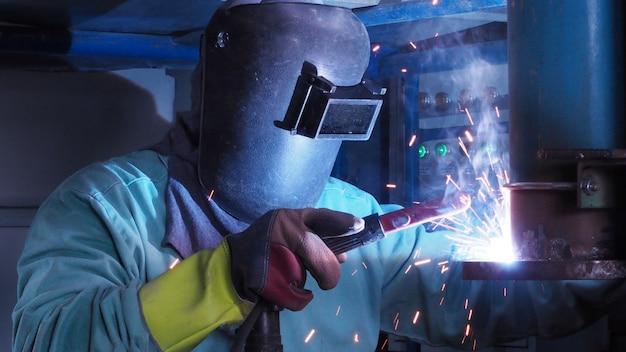Przemysłowy pracownik spawa kołnierza stalowej rury