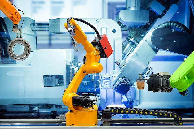 Przemysłowy robot spawalniczy i robot chwytający pracujący z częściami metalowymi w inteligentnej fabryce, na ścianie w kolorze niebieskim maszyny