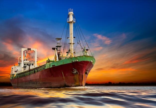 Przemysłowy statek oceaniczny na tle zachodu słońca