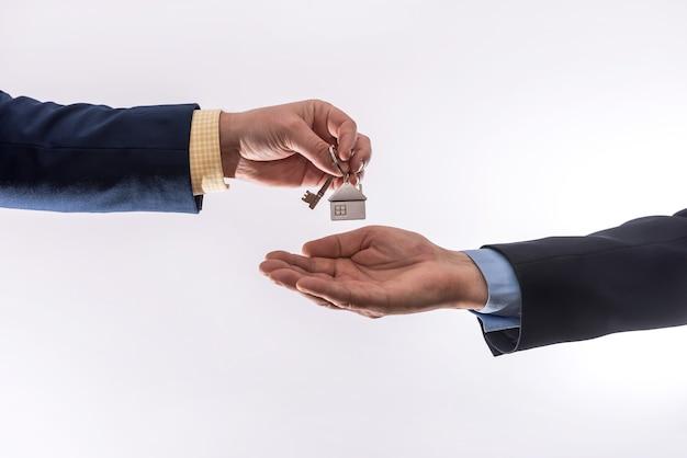 Przeniesienie domu między dwoma biznesmenami wynajmującymi lub sprzedającymi mieszkanie na białej powierzchni