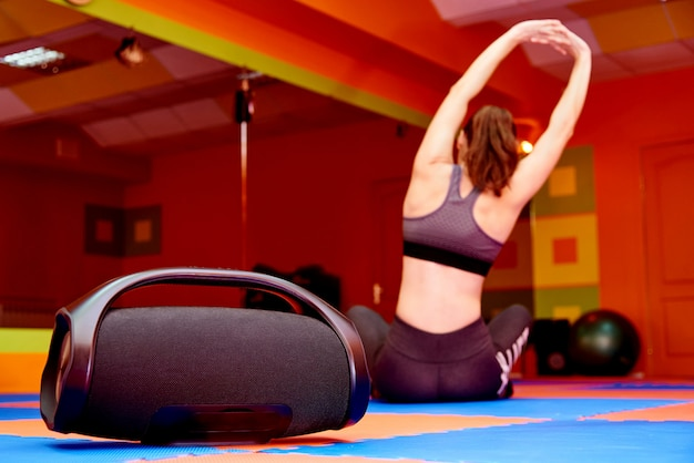 Przenośna akustyka w pokoju aerobiku na tle niewyraźnej dziewczyny uprawiającej sport.