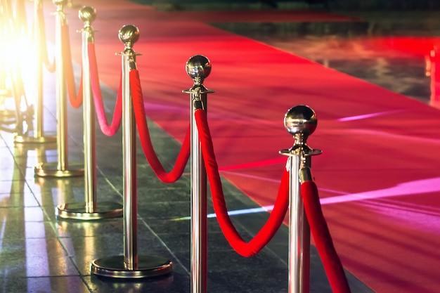 Przenośna bariera do kontroli kolejki. czerwona lina bezpieczeństwa przy czerwonym dywanie.