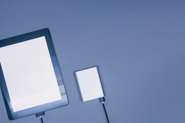 Przenośna ładowarka ładuje makieta tablet z białym ekranem na białym tle na szarym tle.