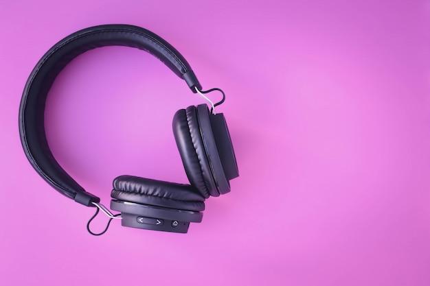 Przenośne czarne słuchawki na różowym tle.