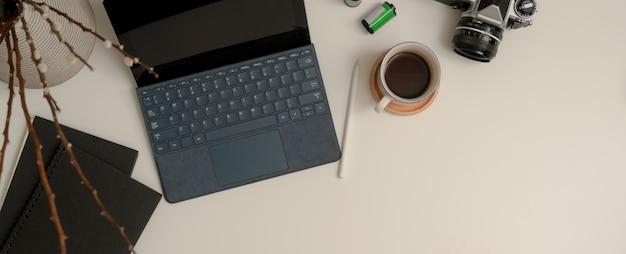 Przenośne miejsce do pracy z cyfrowym tabletem, aparatem, filiżanką kawy, notatnikami, miejscem do dekoracji i kopiowania