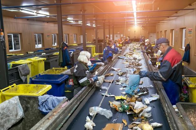 Przenośnik do sortowania odpadów śmieci według ludzi. przetwarzanie śmieci