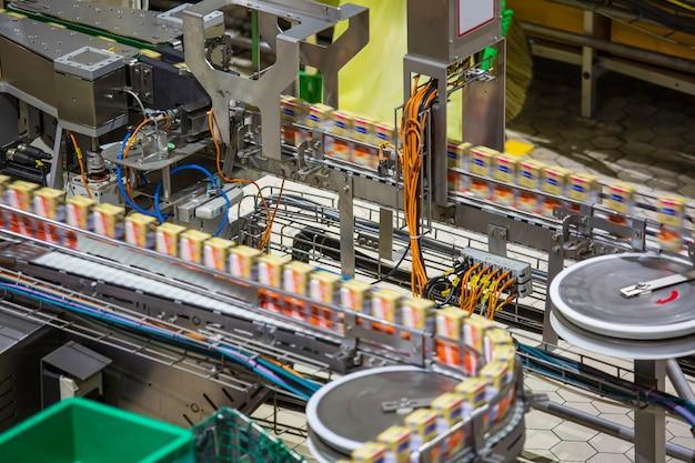 Przenośnik taśmowy, mleko w butelkach na wytwórni napojów lub wnętrza fabryki w przemysłowej linii produkcyjnej.