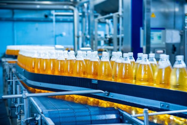 Przenośnik taśmowy z butelkami na sok lub wodę w nowoczesnej wytwórni napojów