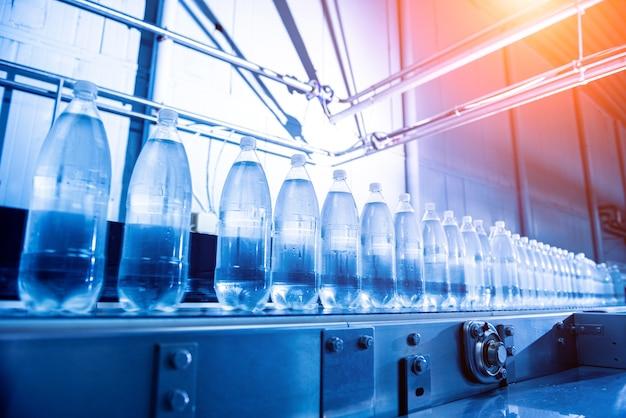 Przenośnik taśmowy z butelkami wody pitnej w nowoczesnym zakładzie napojów.