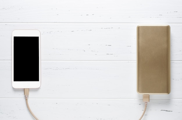 Przenośny władza bank, smartphone na białym drewnie i