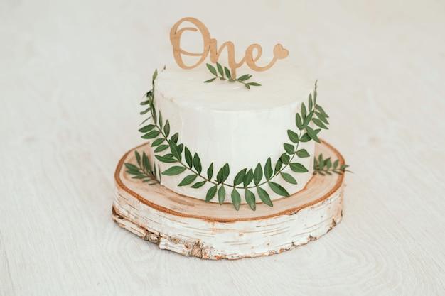 Przepiękny tort z białym serkiem z zielonymi liśćmi. ręcznie robione ciasto dla rocznego dziecka. minimalistyczny tort w stylu rustykalnym. zdjęcie wysokiej jakości