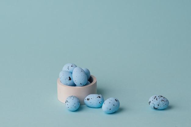 Przepiórki niebieskie pisanki na niebieskim tle. minimalne połączenie z miejscem na kopię. wystrój wiosennych wakacji