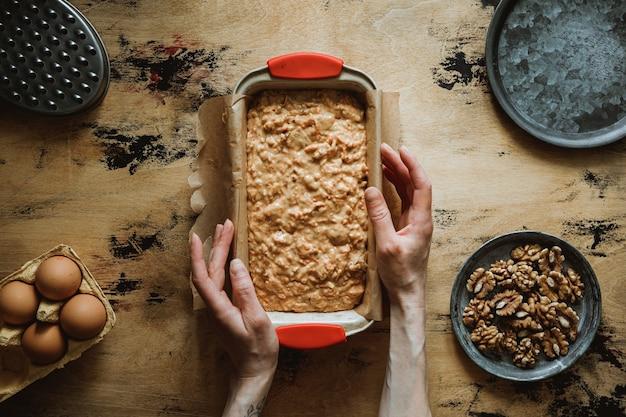 Przepis na ciasto jabłkowo-marchewkowo-orzechowe. ciasto w formie do pieczenia. ręce w kadrze.