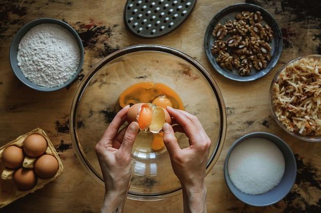Przepis na ciasto jabłkowo-marchewkowo-orzechowe. dodanie jajka do miski. składniki na drewnianym stole. mąka, cukier, jajka. tarka.