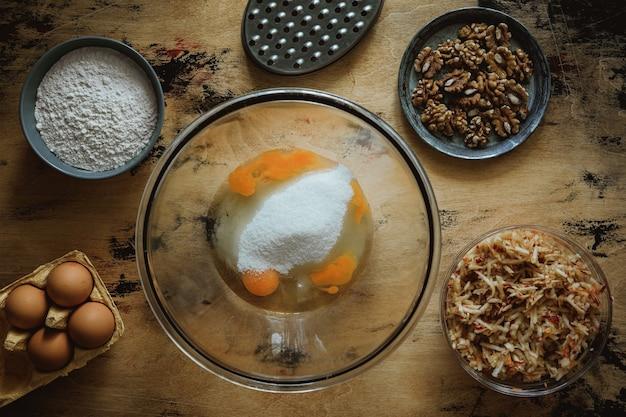 Przepis na ciasto jabłkowo-marchewkowo-orzechowe. jajka i cukier w misce. składniki na drewnianym stole. mąka, jajka, tarka.