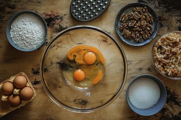 Przepis na ciasto jabłkowo-marchewkowo-orzechowe. jajka w misce. składniki na drewnianym stole. mąka, cukier, jajka. tarka.