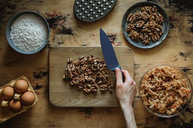 Przepis na ciasto jabłkowo-marchewkowo-orzechowe. siekanie orzechów włoskich na drewnianej desce do krojenia nożem.