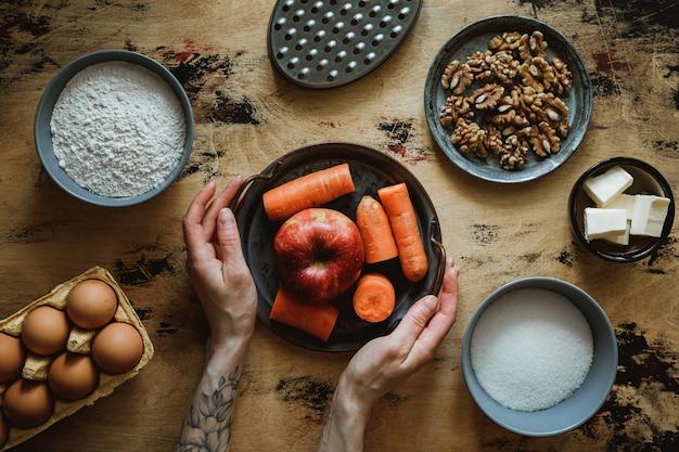 Przepis na ciasto jabłkowo-marchewkowo-orzechowe. składniki na drewnianym stole. mąka, cukier, masło, jajka. tarka. ręce na ramie.