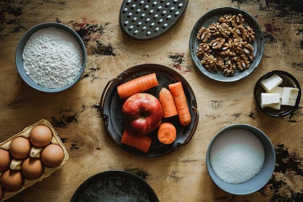 Przepis na ciasto jabłkowo-marchewkowo-orzechowe. składniki na drewnianym stole. mąka, cukier, masło, jajka. tarka.
