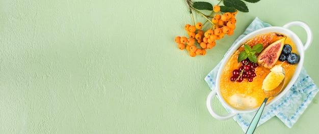 Przepis na deser creme brulee ze świeżymi figami, jagodami i porzeczkami na zielonym kamiennym stole w jesiennej kompozycji, kopia przestrzeń. widok z góry. baner
