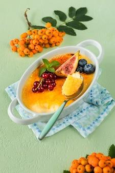 Przepis na deser creme brulee ze świeżymi figami, jagodami i porzeczkami na zielonym kamiennym stole w jesiennej kompozycji.