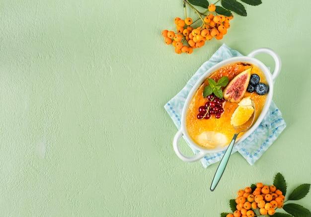 Przepis na deser creme brulee ze świeżymi figami, jagodami i porzeczkami na zielonym kamiennym stole.