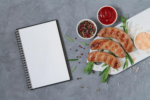Przepis na grillowane kiełbaski z grilla. grill kiełbasa z ziołami, sosem i przyprawami obok otwartego pustego notatnika odgórnego widoku na kamiennym tle