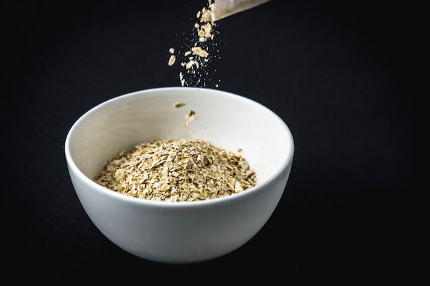 Przepis na płatki owsiane z orzechami, suszonymi śliwkami, cynamonem i cukrem. najpierw wrzuć płatki owsiane do filiżanki