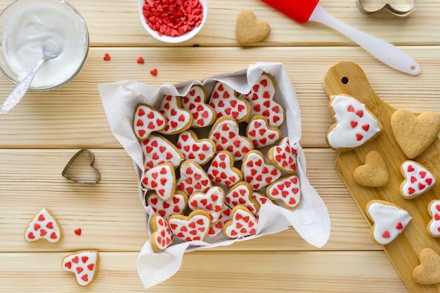 Przepis na robienie ciasteczek na walentynki krok po kroku. ciastka z lukrem i słodką posypką w pudełku.