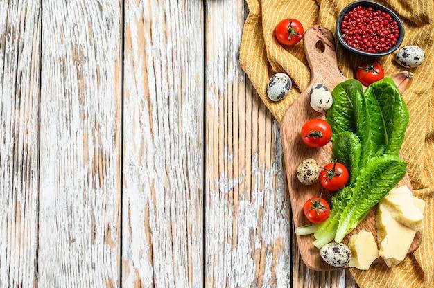 Przepis na sałatkę cezar, sałatę rzymską, pomidory, jajka, parmezan, czosnek, pieprz. widok z góry. skopiuj miejsce