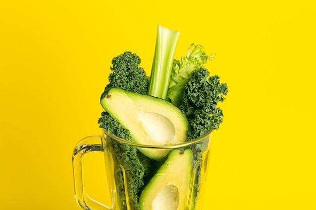 Przepis na smoothie. zielony koktajl warzyw (awokado, seler, sałatka z jarmużu, szpinak) w blenderze na żółtym tle. koncepcja detoksykacji wegańskiej i zdrowej żywności