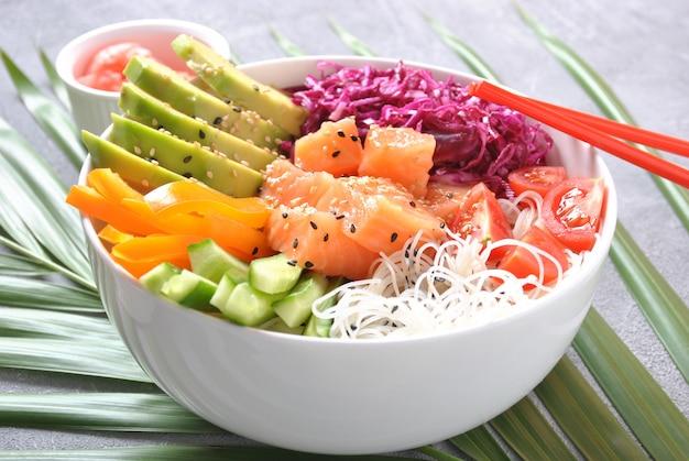 Przepis na świeże owoce morza. jedzenie organiczne. miska ze świeżego łososia z kryształowym makaronem, świeżą czerwoną kapustą, awokado, pomidorami koktajlowymi. miska poke koncepcja żywności