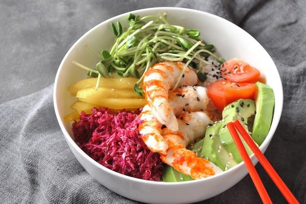 Przepis na świeże owoce morza. krewetki poke bowl z ryżem, czerwoną kapustą, awokado, żółtą słodką papryką