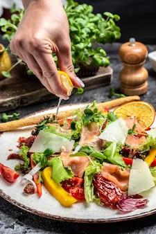 Przepis na świeże owoce morza. łosoś wędzony, sałata, suszone pomidory i sos serowy. zamrozić ruch splash krople soku z cytryny, zdrowa żywność,