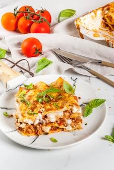 Przepis na włoskie jedzenie. kolacja z klasyczną lasagne bolognese z sosem beszamelowym, parmezanem, bazylią i pomidorami, na białym marmurowym stole,