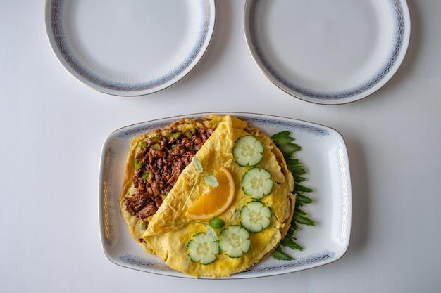 Przepis żywności omlet smażony z kotletami wieprzowymi na stole