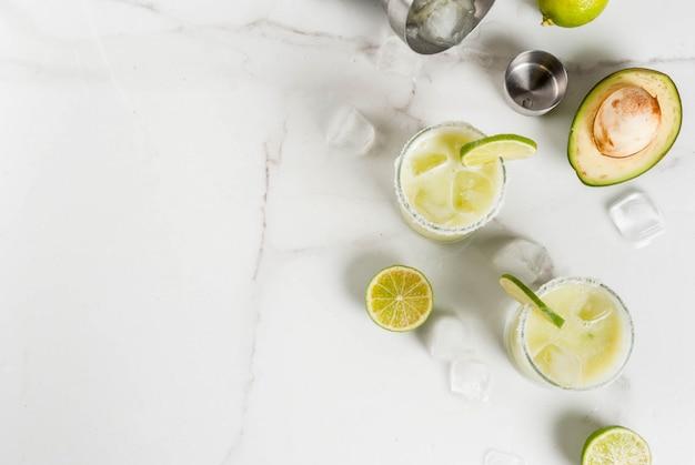 Przepisy i pomysły na koktajle alkoholowe. margaryna awokado i limonka z solą, na kuchennym stole z białego marmuru. widok z góry lato