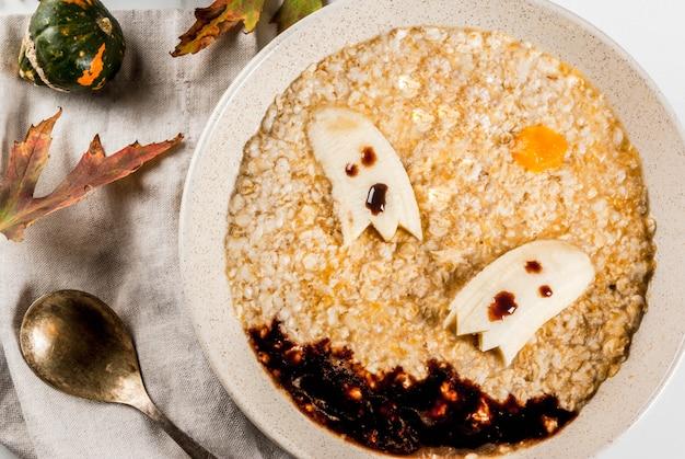 Przepisy na halloween dla dzieci, śniadanie dla dzieci ze słodką owsianką dyniową z przerażającymi jadalnymi duchami bananowymi i sosem czekoladowym